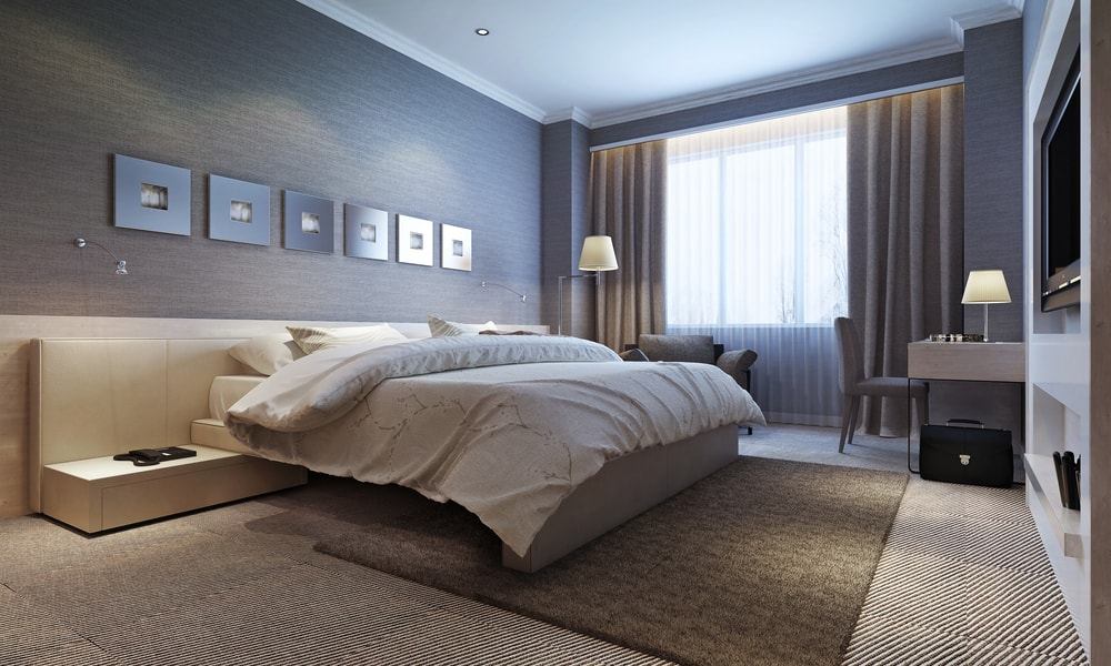 a cozy neutral tone bedroom with carpet floors and area rug